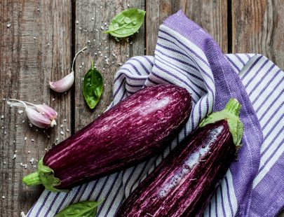 Purple eggplant (aubergine), garlic and basil leaves on vintage wooden table from above. Fresh harvest from the garden in rustic kitchen. Background layout with free text space.